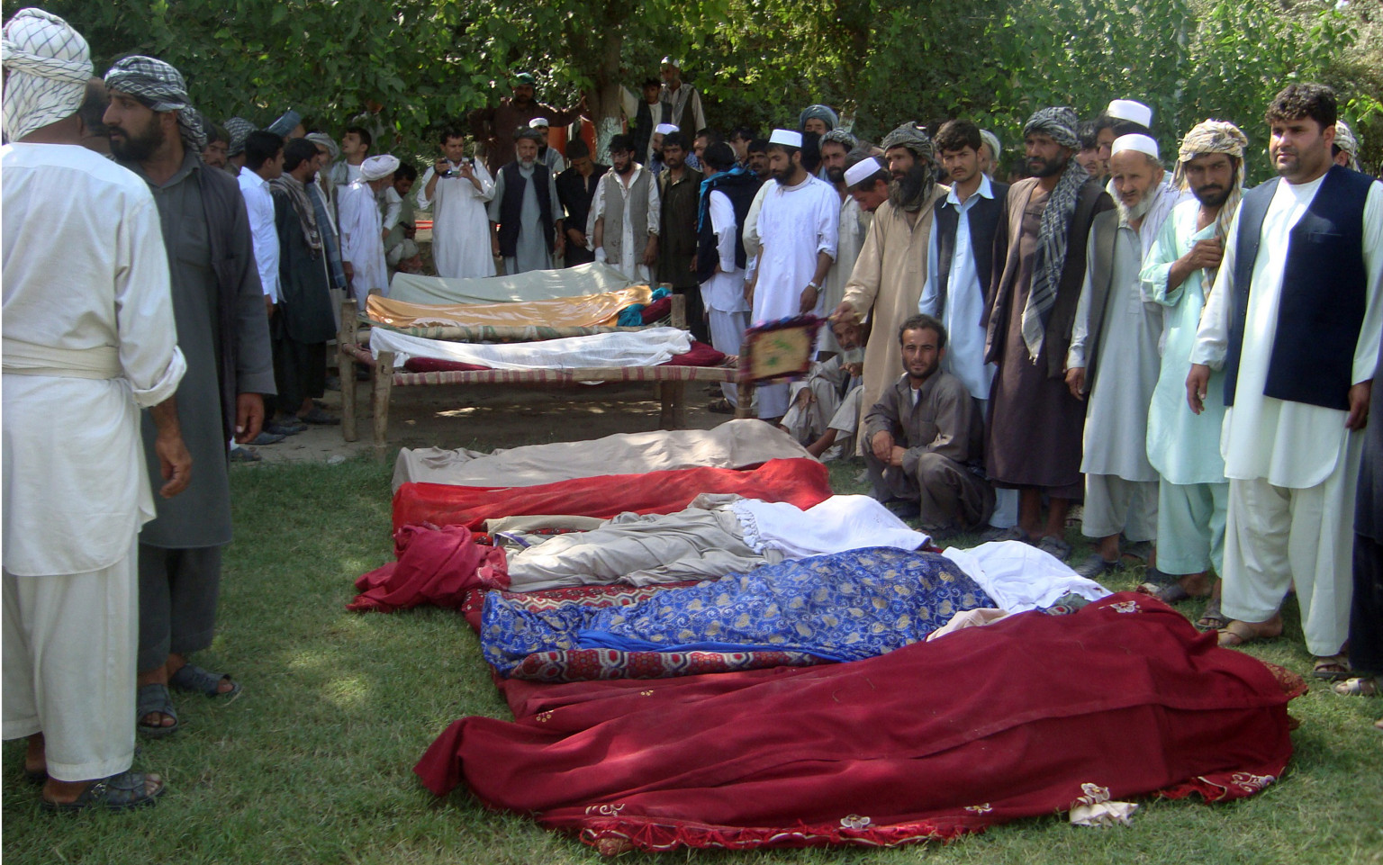 Afghan mourners gather beside bodies of civilians ahead of a funeral ceremony in Kunduz province on September 2, 2012. A pro-government Afghan militia commander and his men have shot dead at least eight civilians in revenge, after mistakenly blaming villagers for a Taliban attack, officials said. AFP PHOTO/ Gul Rahim        (Photo credit should read GUL RAHIM/AFP/GettyImages)